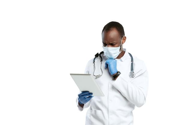 슬픈 독서 뉴스. 흰색 스튜디오에 청진 기 및 얼굴 마스크 남성 젊은 의사.
