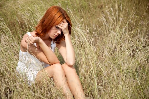 草で悲しい赤毛の少女。