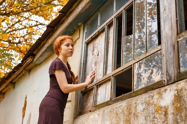 Sad red-haired girl standing near a broken window, the concept of poverty and misery