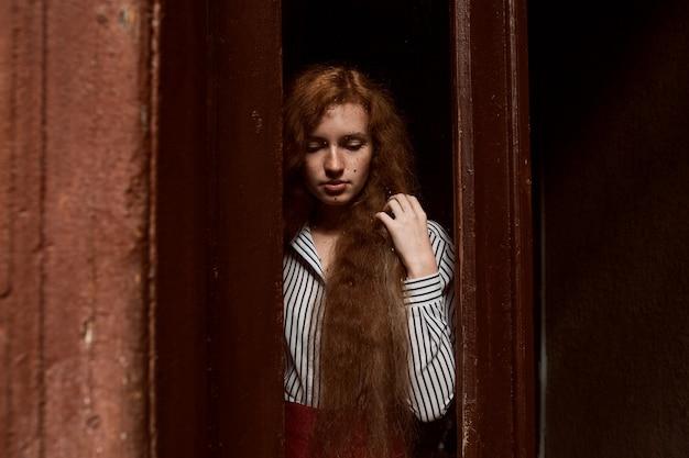 닫힌 유리문 뒤에 서 있는 슬픈 빨간 머리 모델. 유리에 빗방울
