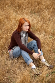 Sad redhead girl sitting on yellow grass at countryside
