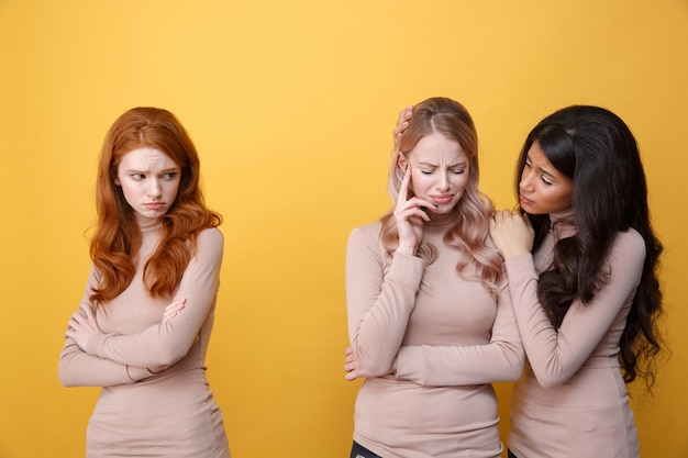 Sad redhead lady looking at african woman calms blonde lady