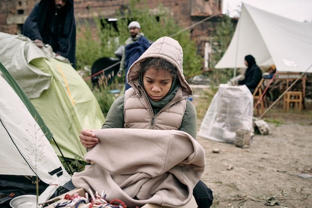 Sad refugee girl with plaid