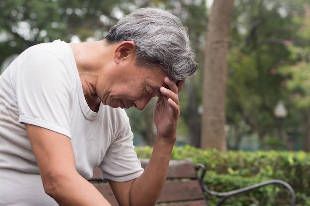 Печальный пенсионер старший мужчина сидит в общественном парке