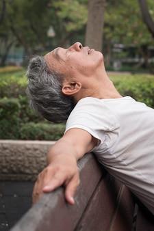 公共の公園で座っている悲しい引退した年配の男性