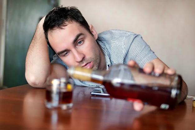 Грустный грустный молодой алкоголик сидит за столом с бутылкой рома. лицо пьяного мужчины. глупая эмоция. депрессия и алкоголизм.