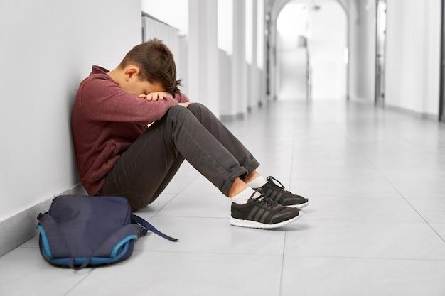 Sad school boy sitting alone on floor at corridor.