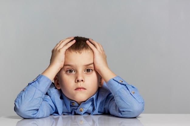 Грустный школьник сидит за столом и держит голову