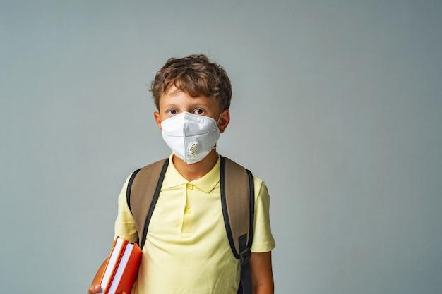 Грустный школьник в защитной маске с рюкзаком
