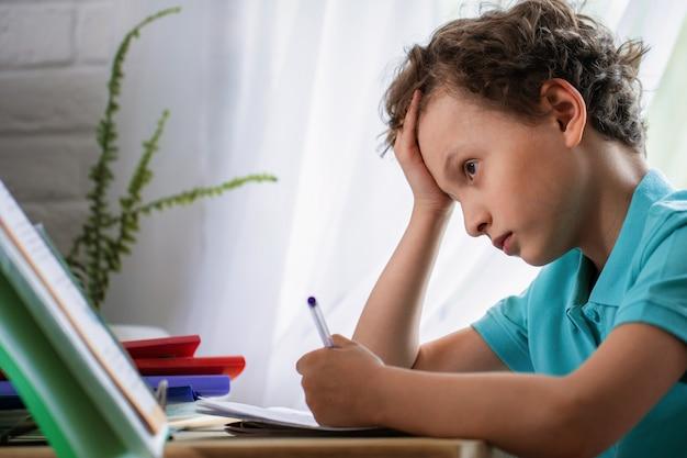 悲しい男子生徒が頭の下に手を置いて本を見る
