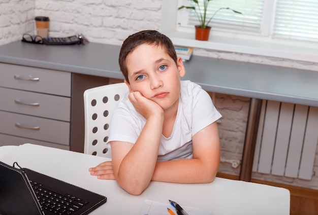 집에서 책상에 혼자 앉아 슬픈 모범생. 심술 불만족 소년