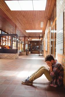 廊下に一人で座っている悲しい少年