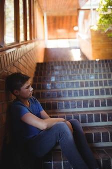 Грустный школьник сидит один на лестнице