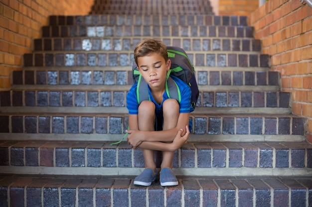 Sad schoolboy sitting alone in staircase