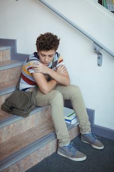 Sad schoolboy sitting alone on staircase