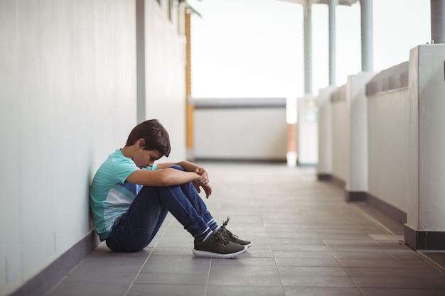 Грустный школьник сидит в коридоре