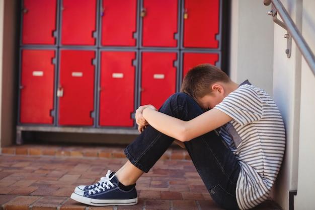 廊下に座っている悲しい少年