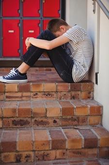 階段の上に座って悲しい少年