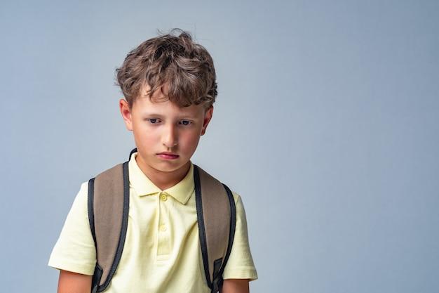 Грустный школьник с рюкзаком изолирован