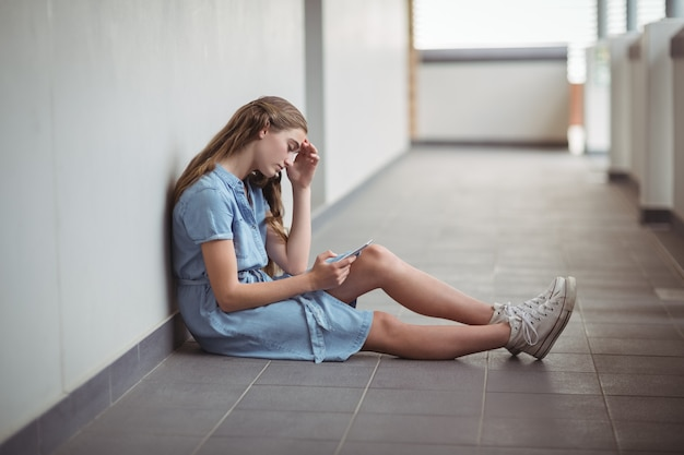 廊下で携帯電話を使用して悲しい女子高生