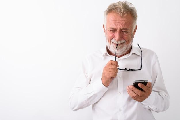 Грустный старший бородатый мужчина плачет, используя мобильный телефон и кусая очки на белом