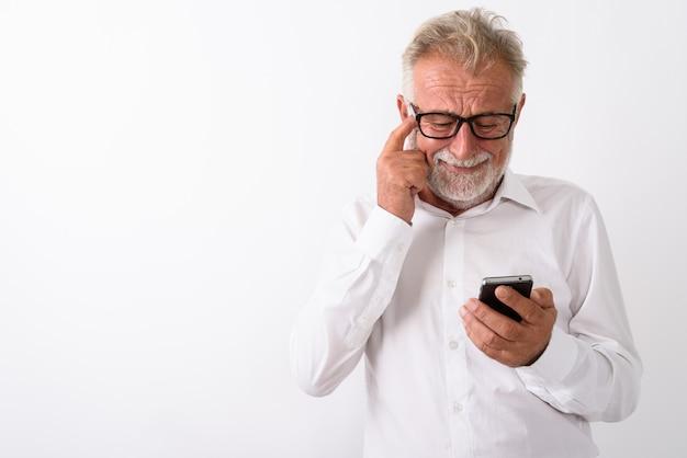 Грустный старший бородатый мужчина с помощью мобильного телефона почесывая голову в очках на белом