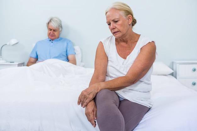 寝室に座っている悲しい年配のカップル