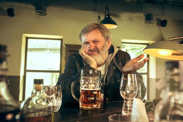 Печальный старший мужчина пьет алкоголь в пабе