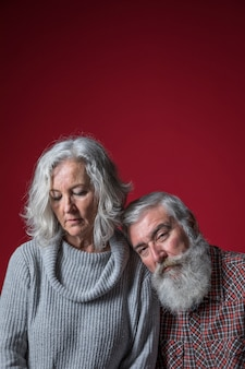 Sad senior man leaning on his wife's shoulder against red backdrop