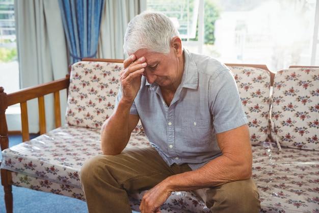 Sad senior man sitting on a couch