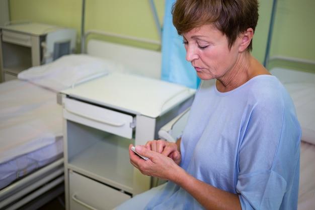 Грустный старший пациент с помощью мобильного телефона