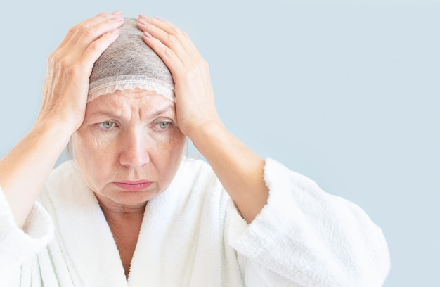 Sad senior woman, her hands on her head, in a cosmetic cap. concept anti age, fatigue, anxiety, thinking about old age and illness
