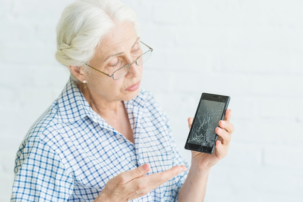 Sad senior woman showing smartphone with broken screen against white backdrop