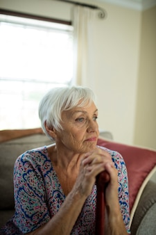 Sad senior woman sitting on couch at home