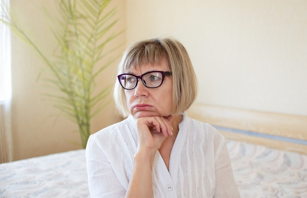 Грустная старшая женщина с белыми волосами в очках грустит в своем доме в спальне. концепция одиночества, тоска, грусть