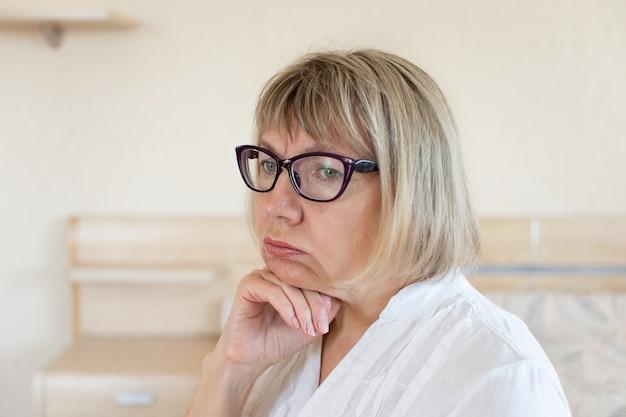 Грустная старшая женщина с белыми волосами грустит в своем доме в спальне.