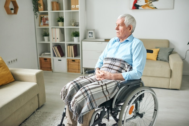 Sad and serene senior disable man with checkered plaid on his knees sitting in wheelchair by couch at home