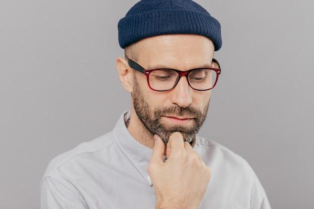 Sad serious male keeps hand under chin, has dark bristle, looks down