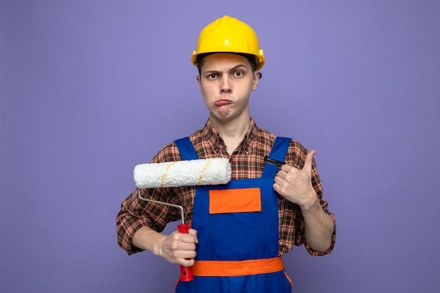 Triste che mostra il pollice in su giovane costruttore maschio che indossa l'uniforme che tiene la spazzola a rullo