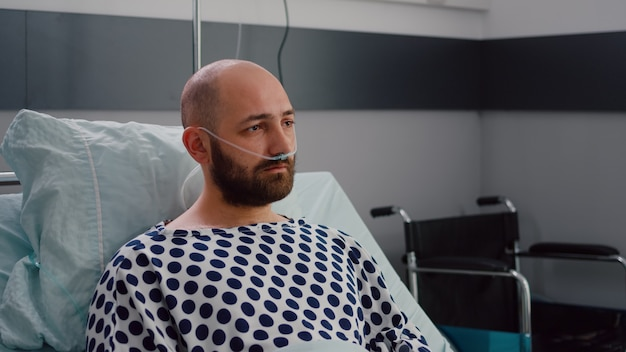 Sad sick man with nasal oxygen tube resting in bad looking into camera