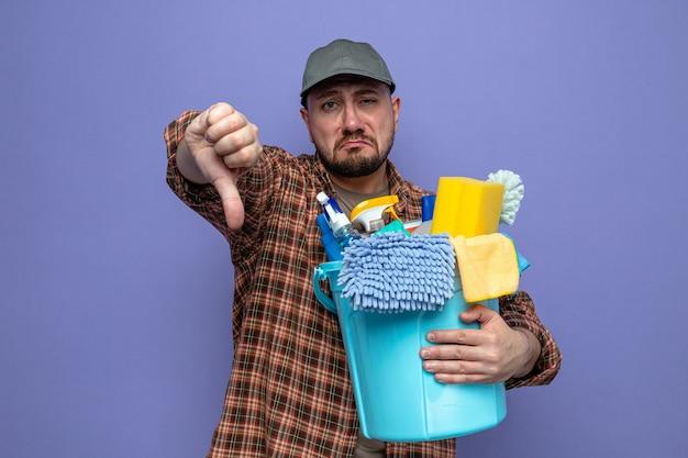 Uomo triste delle pulizie slavo che tiene in mano l'attrezzatura per la pulizia e fa il pollice verso il basso