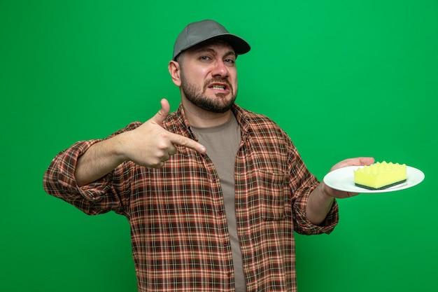 Uomo triste delle pulizie slavo che tiene e indica la spugna sul piatto