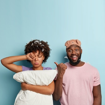 Sad sleepy dark skinned female rubs eyes, wake up early, holds white pillow, wants to sleep more, glad husband wears sleepmask on forehead, points with thumb at tired wife. bad rest concept.