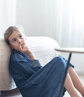 슬픈 졸린 어린 소녀가 소파에 기대어 앉아 있습니다.