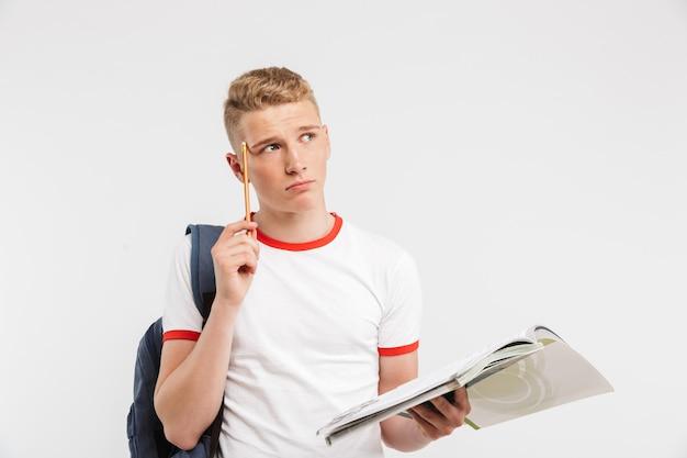 Печальный умный парень, носящий рюкзак, думая и трогая храм с ручкой, изучая и держа в руке учебники, изолированные на белом