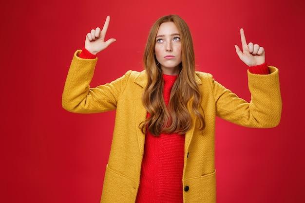 Triste e triste donna rossa carina in cappotto giallo alzando le mani scontento di rimpianto guardando l'angolo in alto a sinistra apatico come deluso dalla pioggia o dal maltempo sul muro rosso.