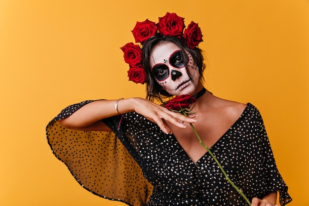 Sad spanish girl in carnival image. photo indoors of lady with crown of roses holding red flower in her hand.