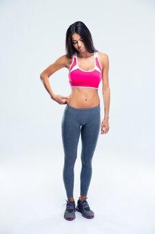 Грустная спортивная женщина трогает жир на животе