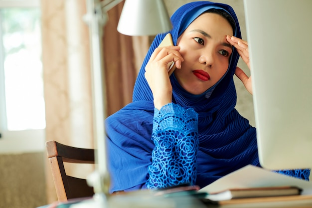 Sad stressed muslim woman calling on phone