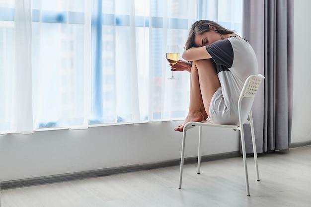 Грустно подчеркнул, несчастлив, подавлен, тоска, молодая пьющая женщина сидит одна дома возле окна и держит бокал во время трудностей, проблем жизни и депрессии.